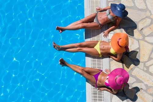 Three-women-in-bikini-wearing-a-straw-hat-by-the-swimming-pool-img-blog