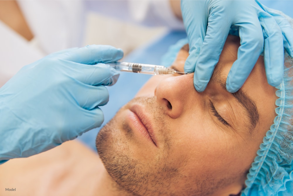 Man undergoing a BOTOX® Cosmetic injection between the eyebrows with his plastic surgeon.